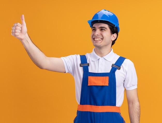 Uomo giovane costruttore in uniforme da costruzione e casco di sicurezza che guarda da parte con il sorriso sul viso che mostra i pollici in su in piedi sopra la parete arancione