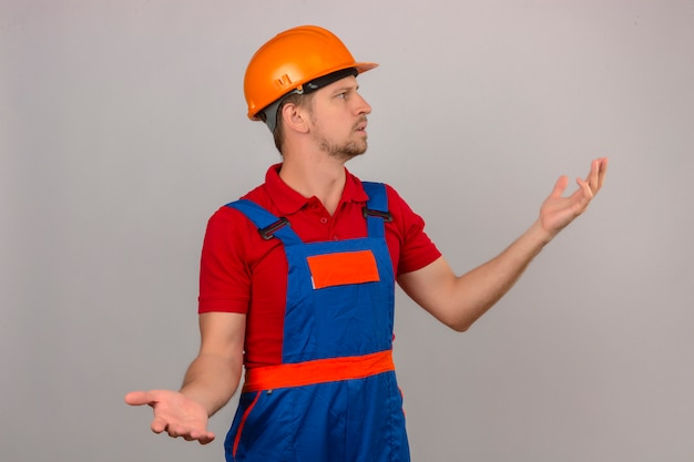 Young builder man in construction uniform and safety helmet looking away making confused gesture with hands and expression as asking question over isolated white wall