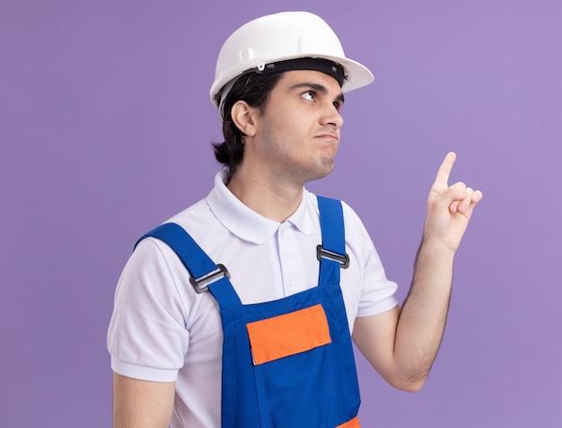 Uomo giovane costruttore in uniforme da costruzione e casco di sicurezza che sembra confuso indicando con il dito indice a lato in piedi sopra la parete viola