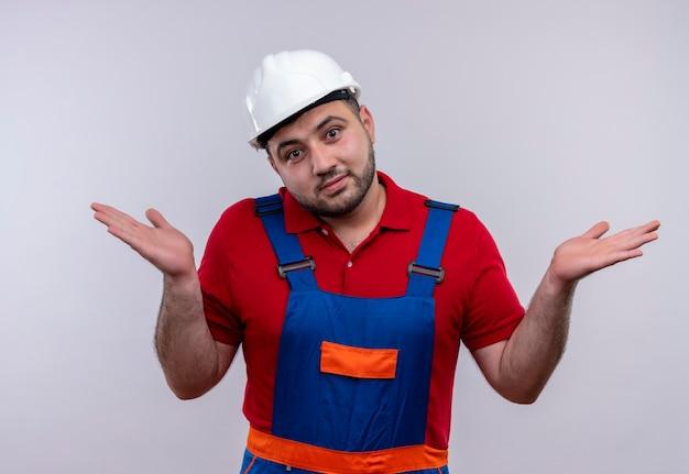 Giovane costruttore in uniforme da costruzione e casco di sicurezza che sembra confuso e incerto senza risposta