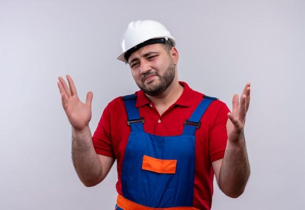 Giovane costruttore in uniforme da costruzione e casco di sicurezza che sembra confuso con l'espressione infastidita alzando le braccia