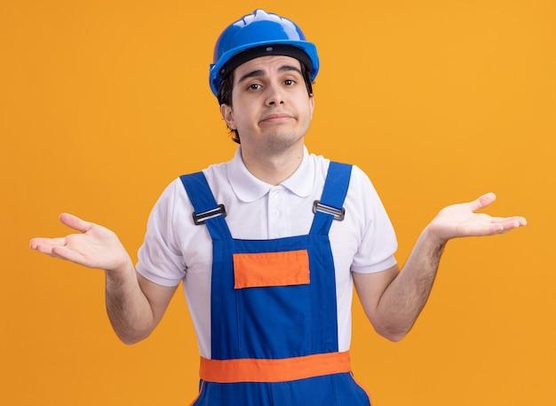 Giovane costruttore in uniforme da costruzione e casco di sicurezza guardando davanti confuso diffondendo le braccia ai lati senza risposta in piedi sopra la parete arancione