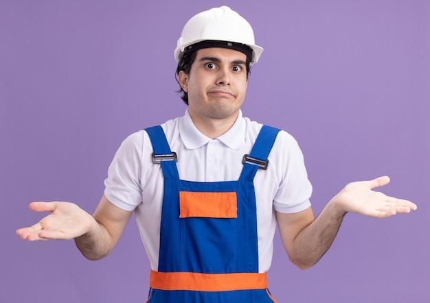 Giovane costruttore in uniforme da costruzione e casco di sicurezza guardando davanti confuso diffondendo le braccia ai lati senza risposta in piedi sopra il muro viola