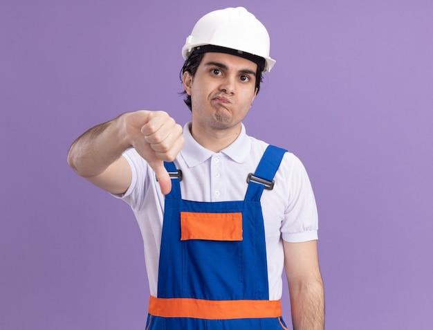 Uomo giovane costruttore in uniforme da costruzione e casco di sicurezza guardando la parte anteriore dispiaciuto mostrando i pollici verso il basso in piedi sul muro viola