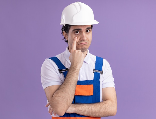 Young builder man in construction uniform and safety helmet looking at front pointing with index finger at his eye being confused standing over purple wall