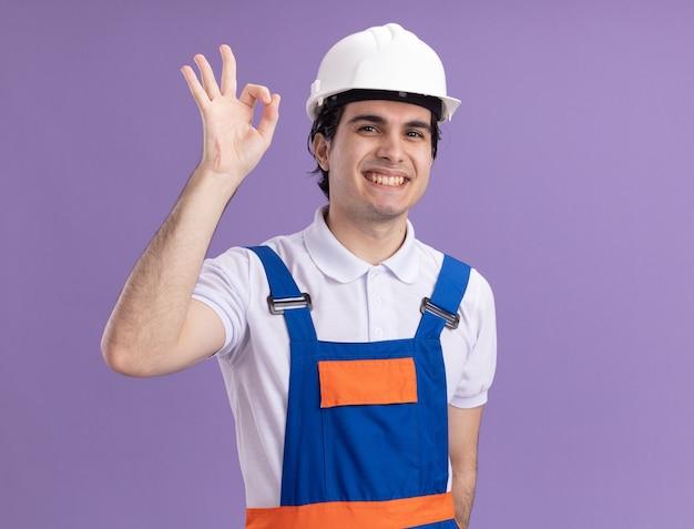 Uomo giovane costruttore in uniforme da costruzione e casco di sicurezza guardando davanti sorridendo allegramente mostrando segno giusto in piedi sopra la parete viola