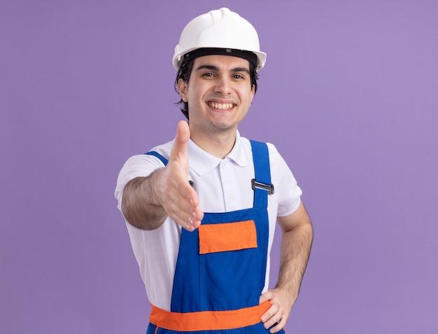 Uomo giovane costruttore in uniforme da costruzione e casco di sicurezza guardando davanti sorridente amichevole che offre saluto a mano in piedi sopra la parete viola