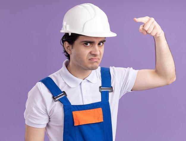 Uomo giovane costruttore in uniforme da costruzione e casco di sicurezza guardando davanti con faccia arrabbiata che punta con il dito indice davanti in piedi sopra la parete viola