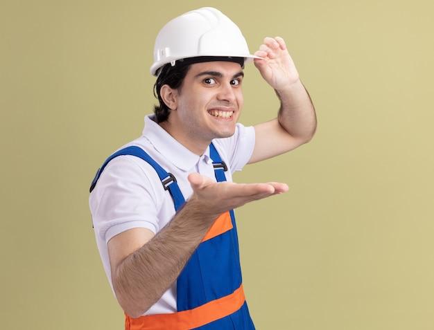 Uomo giovane costruttore in uniforme da costruzione e casco di sicurezza guardando la parte anteriore con il braccio fuori sorridendo allegramente in piedi sopra la parete verde