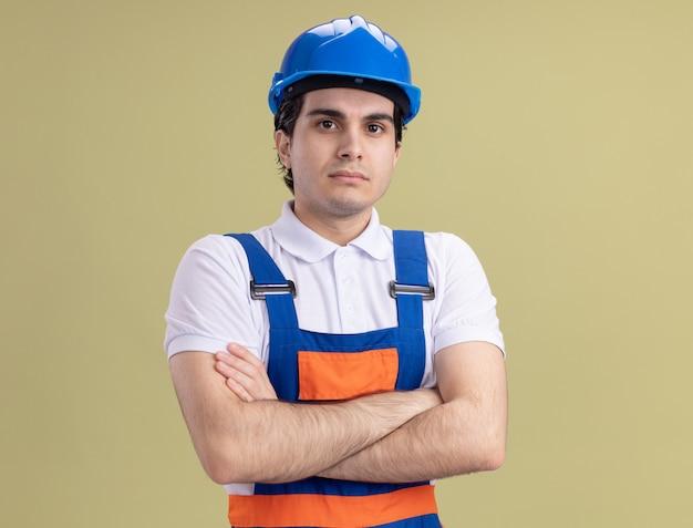Uomo giovane costruttore in uniforme da costruzione e casco di sicurezza guardando davanti con espressione fiduciosa con le braccia incrociate in piedi sopra la parete verde