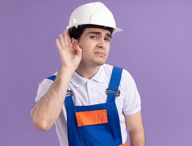 Uomo giovane costruttore in uniforme da costruzione e casco di sicurezza guardando la parte anteriore con la mano sull'orecchio cercando di ascoltare i pettegolezzi in piedi sopra il muro viola