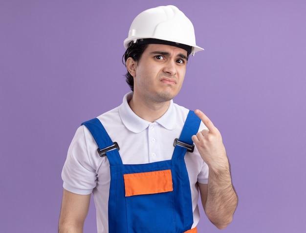 Uomo giovane costruttore in uniforme da costruzione e casco di sicurezza guardando davanti con espressione triste confusa indicando se stesso in piedi sopra il muro viola