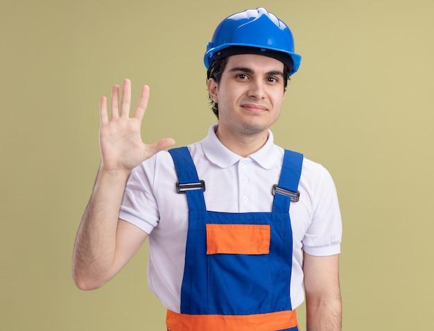 Uomo giovane costruttore in uniforme da costruzione e casco di sicurezza guardando la parte anteriore con il sorriso sul viso che fluttua con la mano in piedi sopra la parete verde