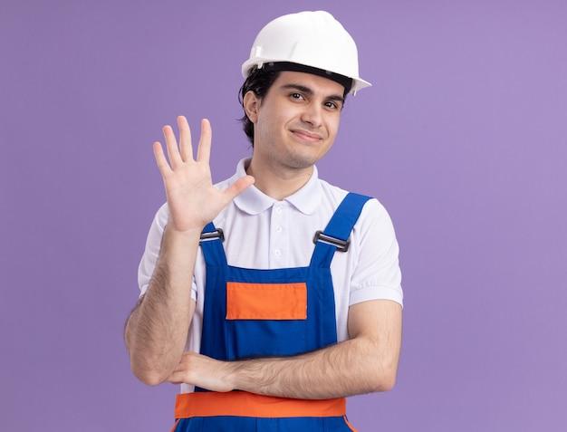 Uomo giovane costruttore in uniforme da costruzione e casco di sicurezza guardando la parte anteriore con il sorriso sul viso che fluttua con la mano in piedi sopra la parete viola