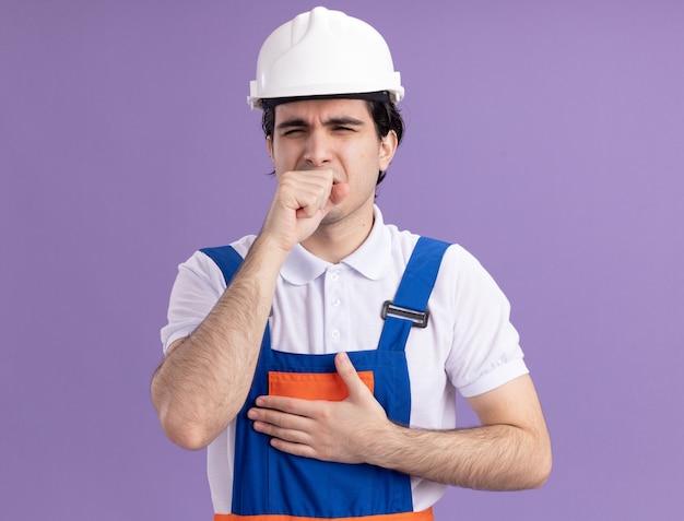 Uomo giovane costruttore in uniforme da costruzione e casco di sicurezza che sembra malato tosse in piedi sopra la parete viola