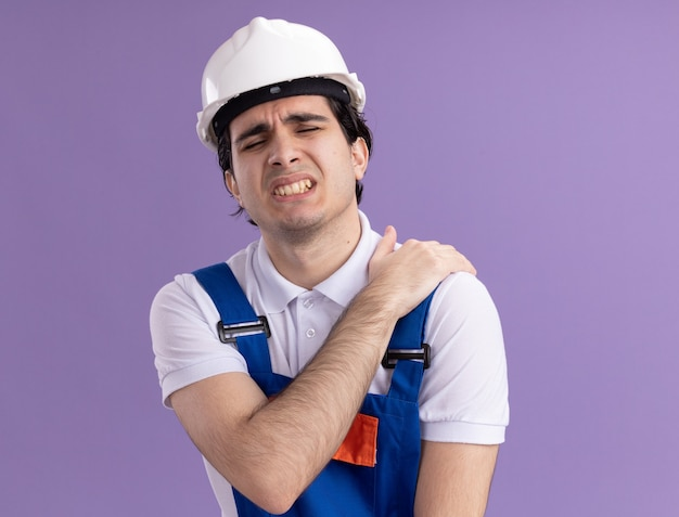 Young builder man in construction uniform and safety helmet looking unwell touching his shoulder feeling pain standing over purple wall