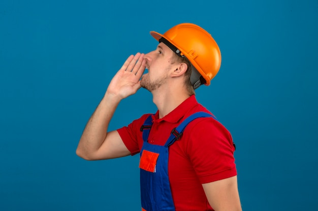 Young builder man in construction uniform and safety helmet looking up and shouting angry out loud with hand over mouth standing sideways over isolated blue wall