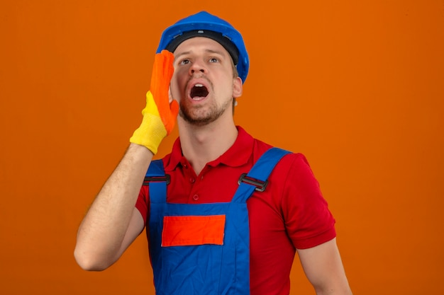 Young builder man in construction uniform and safety helmet looking up and shouting angry out loud with hands over mouth over isolated orange wall