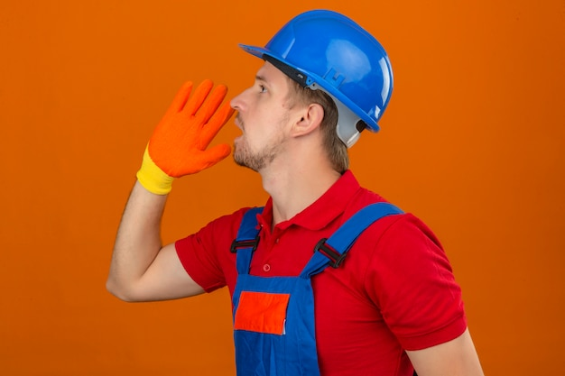 Young builder man in construction uniform and safety helmet looking up and shouting angry out loud with hands over mouth standing sideways over isolated orange wall