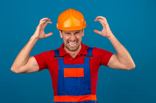 Young builder man in construction uniform and safety helmet mad shouting and yelling with aggressive expression and arms raised over isolated blue wall