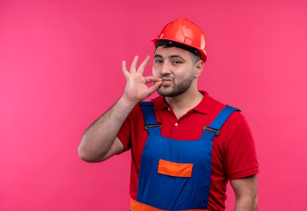 Young builder man in construction uniform and safety helmet making silence gesture like closing mouth with a zipper