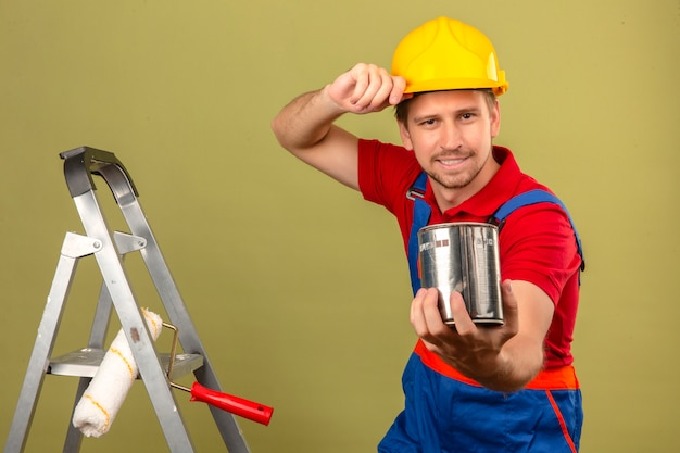 Young builder man in construction uniform and safety helmet on metal ladder holding paint can presenting to camera over isolated green wall