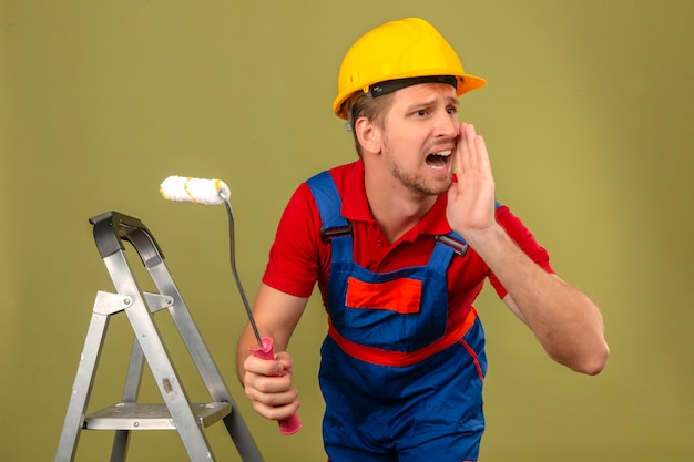 Young builder man in construction uniform and safety helmet on metal ladder holding paint roller and shouting angry out loud with hand over mouth over isolated green wall