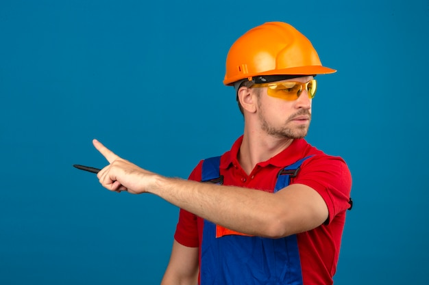 Young builder man in construction uniform and safety helmet pointing with index finger to the side over isolated blue wall