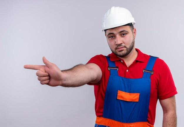 Uomo giovane costruttore in uniforme da costruzione e casco di sicurezza che punta con il dito indice ai lati con faccia seria