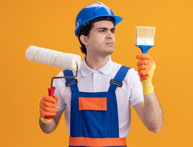 Uomo giovane costruttore in uniforme da costruzione e casco di sicurezza in guanti di gomma che tengono rullo di vernice e pennello che sembrano confusi in piedi sopra la parete arancione