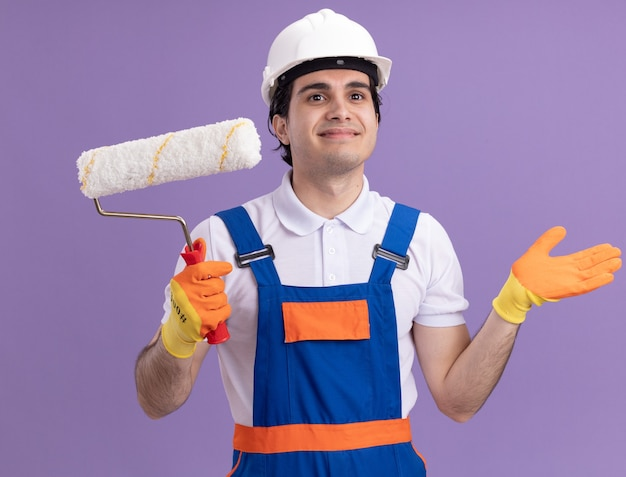 Uomo del giovane costruttore in uniforme da costruzione e casco di sicurezza in guanti di gomma che tengono il rullo di vernice che osserva da parte con il sorriso sul viso in piedi sopra la parete viola