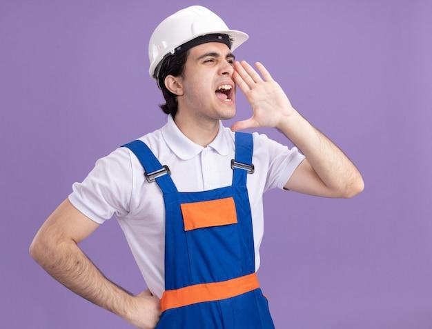 Giovane costruttore in uniforme da costruzione e casco di sicurezza che grida o chiama qualcuno con la mano vicino alla bocca in piedi sopra il muro viola
