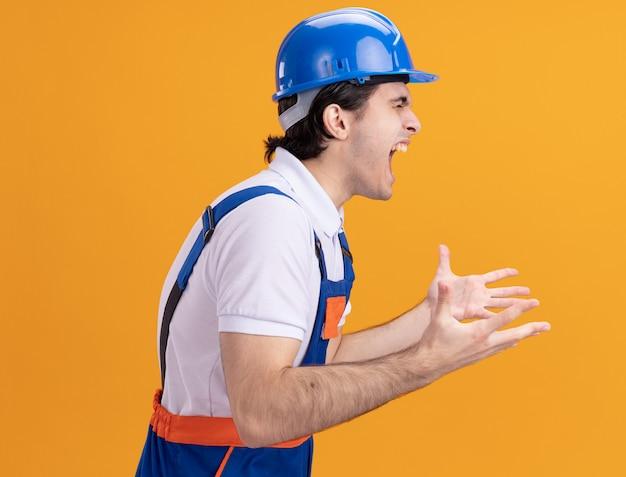 Uomo giovane costruttore in uniforme da costruzione e casco di sicurezza che grida con espressione aggressiva in piedi sopra la parete arancione