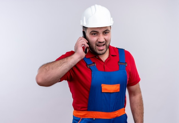 Young builder man in construction uniform and safety helmet shouting with aggressive expression while talking on mobile phone