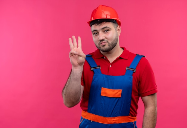 Uomo giovane costruttore in uniforme da costruzione e casco di sicurezza che mostra e rivolto verso l'alto con le dita numero tre