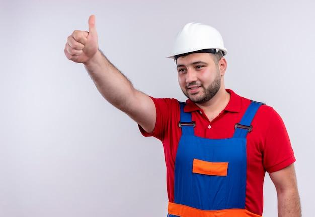 Uomo giovane costruttore in uniforme da costruzione e casco di sicurezza che mostra i pollici in su sorridente