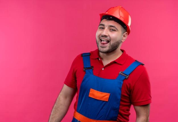 Uomo del giovane costruttore in uniforme della costruzione e casco di sicurezza che sorride allegramente che attacca fuori linguetta