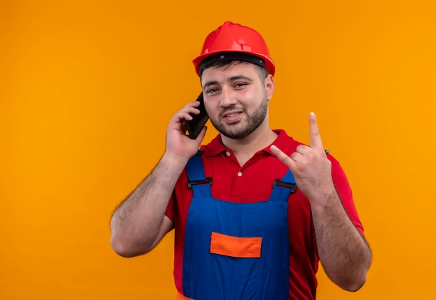 Uomo giovane costruttore in uniforme da costruzione e casco di sicurezza che sorride facendo il simbolo della roccia con le dita mentre parla al telefono cellulare