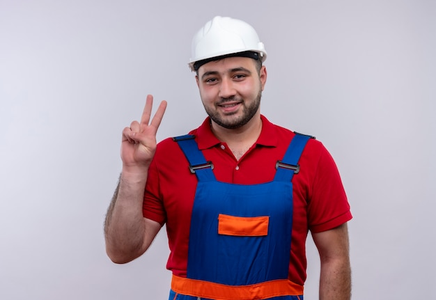 Young builder man in construction uniform and safety helmet smiling showing and pointing up with fingers number two