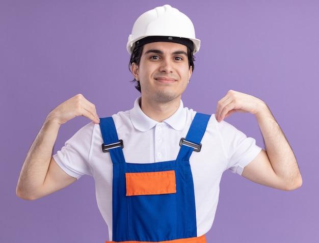 Uomo del giovane costruttore in uniforme da costruzione e casco di sicurezza che sorride con la faccia felice che solleva le mani che tocca le sue spalle che stanno sopra la parete viola