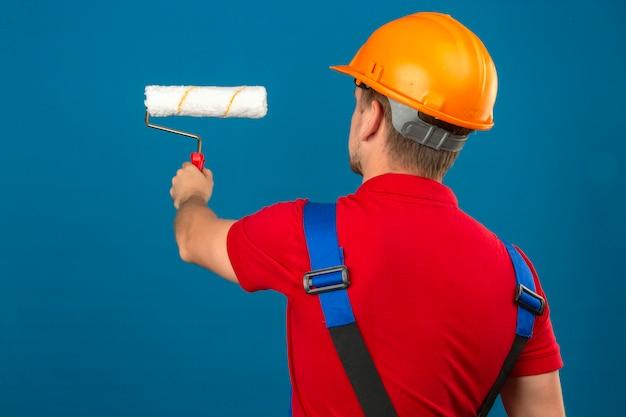 Giovane uomo del costruttore in uniforme della costruzione e casco di sicurezza che stanno indietro con il rullo di pittura sopra la parete blu isolata