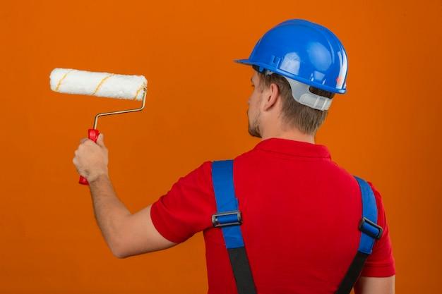 Giovane uomo del costruttore in uniforme della costruzione e casco di sicurezza che stanno indietro con il rullo di pittura sopra la parete arancio isolata