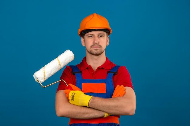 Giovane uomo del costruttore in uniforme della costruzione e casco di sicurezza che stanno con le armi attraversate con il rullo di pittura che sembra sicuro sopra la parete blu isolata