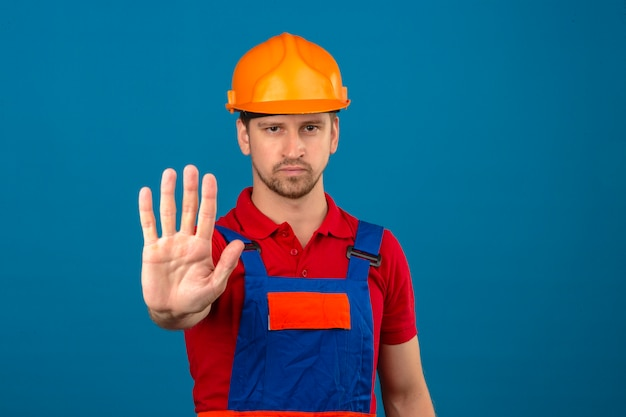 Young builder man in construction uniform and safety helmet standing with open hand doing stop sign with serious and confident expression defense gesture over isolated blue wall
