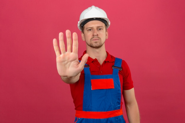Young builder man in construction uniform and safety helmet standing with open hand doing stop sign with serious and confident expression defense gesture over isolated pink wall