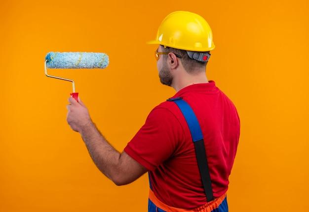 Uomo giovane costruttore in uniforme da costruzione e casco di sicurezza con la schiena che tiene il rullo di vernice