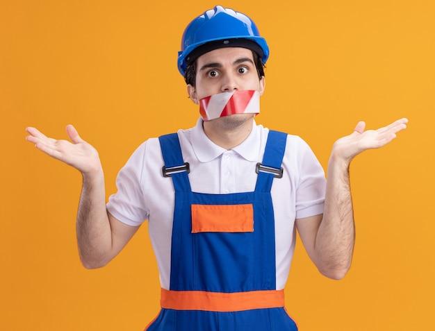 Giovane costruttore in uniforme da costruzione e casco di sicurezza con nastro adesivo avvolto intorno alla bocca che guarda confuso scrollare le spalle in piedi sopra la parete arancione
