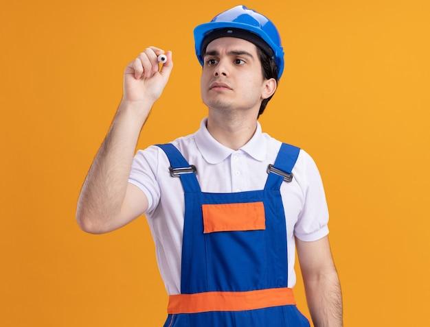 Uomo del giovane costruttore in uniforme da costruzione e casco di sicurezza che scrive con la penna davanti alla parte anteriore con la faccia seria che sta sopra la parete arancione