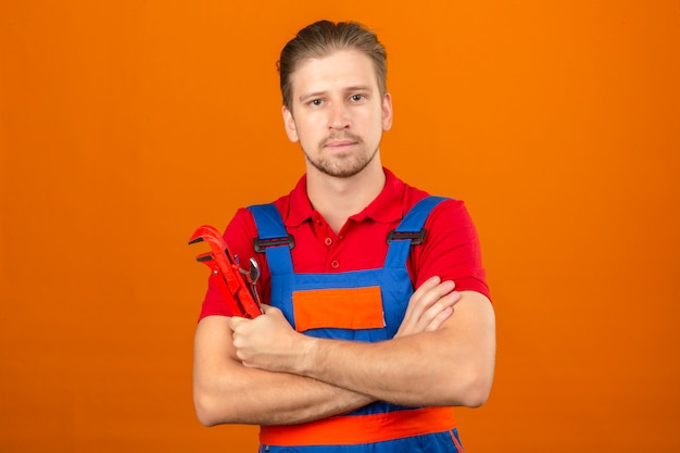 Giovane uomo del costruttore in uniforme della costruzione con il sorriso sicuro sul fronte e le braccia attraversate con la chiave inglese a disposizione sopra la parete arancione isolata
