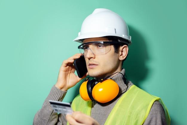 若いビルダーの男、エンジニア、電話でクレジットカードで支払います。アクアメンテカラーの壁に建設安全ヘルメット、眼鏡、ヘッドホンを着用。